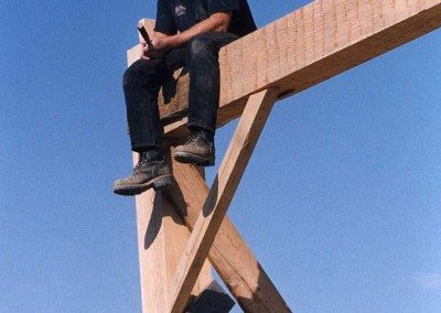 Ronald Babcock rests atop the German Barn's tall frame during restoration, 2001, Photograph by Constance Kheel