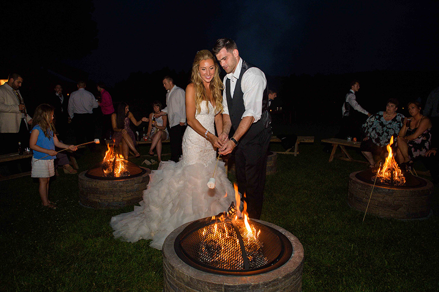 Guests roast marshmallows by campfires during a wedding reception, Tom Wall Photography